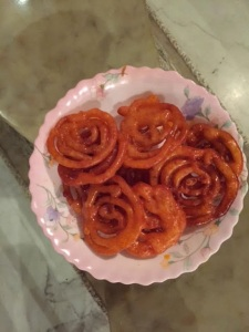 Jalebis , dripping sugar and dipped orange