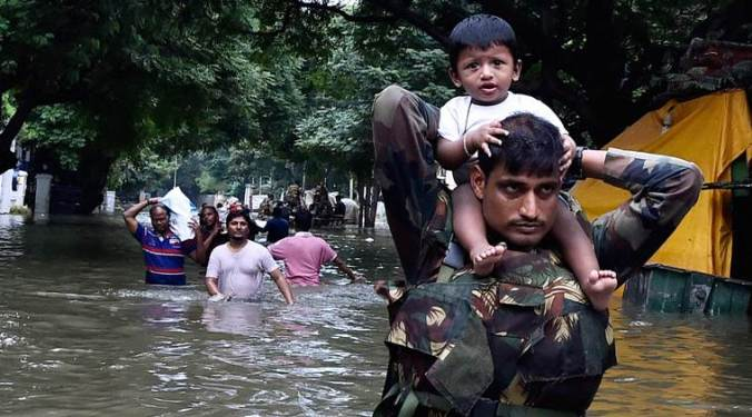 Chennai: Army personnel carry children on their shoulders as they wade through flood waters in rain-hit Chennai on Thursday. PTI Photo(PTI12_3_2015_000387B)