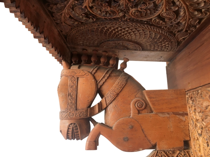 horse bust of galloping horse supporting carved header of carved doorway