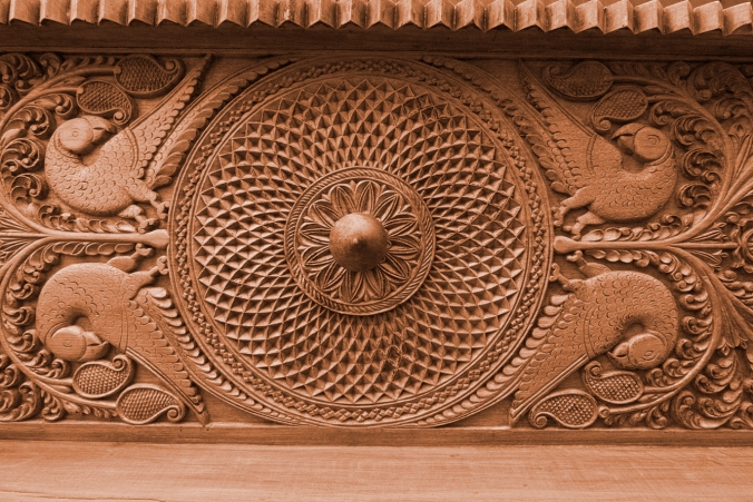 intricately carved header of an 80 year old vintage doorway, the sandalwood room